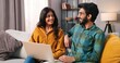 canvas print picture Portrait of young Hindu joyful married couple sitting on sofa in cozy living room browsing online on laptop computer surfing internet choosing something, e-commerce, wife and husband concept