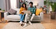 canvas print picture Hindu happy cheerful young married couple sitting on sofa in modern room browsing on laptop computer buying making purchase with credit card, internet shopping, family time, e-commerce concept