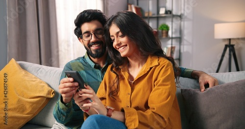 canvas print motiv - VAKSMANV : Portrait of cheerful positive young lovely couple smiling spending time together at home sitting on sofa typing on smartphone, searching internet using social network app on cellphone, family concept