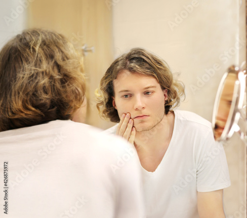 young man looking in the mirror,combing his hair,looking at problems on face.. - fototapety na wymiar