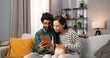 canvas print picture Portrait of joyful mixed-race young man and woman couple sitting on comfortable sofa in cozy room holding cat pet browsing on tablet choosing something online, leisure, social network concept