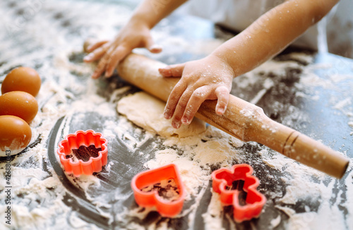 Photo Small hands of child roll out the dough with a rolling pin on a wooden surface