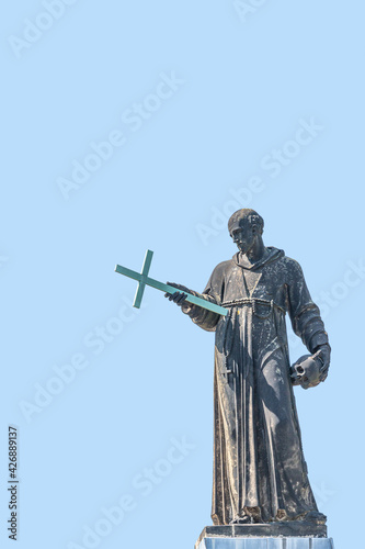 Obraz na plátne Cover page with old roof church statute of high ranked priest with a cross and h