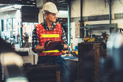 Obraz Manufacturing worker working with clipboard to do job procedure checklist . Factory production line occupation quality control concept . - fototapety do salonu