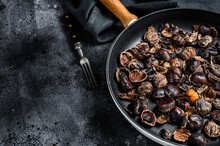 Roast Grilled Chestnuts On A Wooden Table. Black Background. Top View. Copy Space
