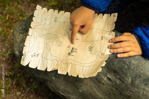 Fotografie, Obraz The child is looking for a treasure on the children's pirate map.