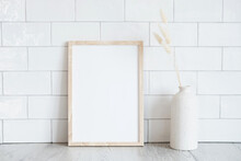 Empty Wooden Frame Mockup And Dried Flowers In Vase On White Tiles Wall Background. Scandinavian Interior, Home Design. Minimal, Elegant Style.