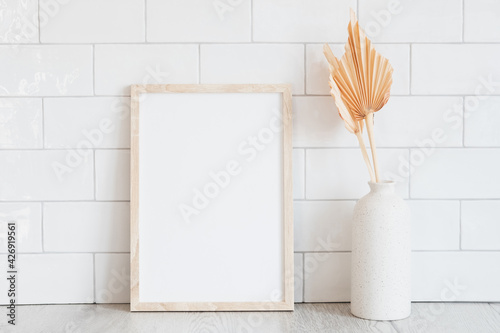 Fotografie, Obraz Wooden vertical picture frame mockup and dried flowers in vase on white tiles wall background