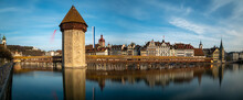 Panoramic View Of The Chapel Bridge In Lucern, Switzerland. Long Exposure With Bridge And City Skyline Reflecting On Water Against Blue Sky.