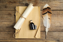 Feather Pen, Bottle Of Ink, Notebook And Parchment Scroll On Wooden Table, Flat Lay