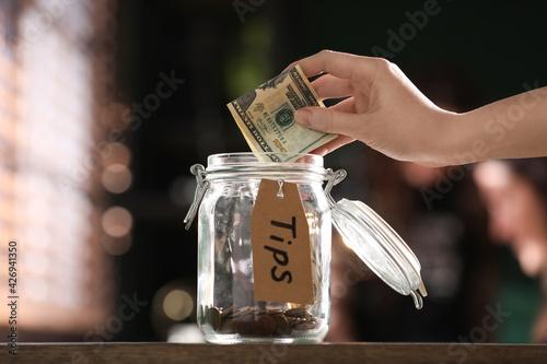 Fotografija Woman putting tips into glass jar on wooden table indoors, closeup