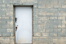 An Exterior Industrial Solid White Metal Door With A Lock And Handle In An Old Grey Concrete Block Wall In A Building. The Gray Blocks' Paint Is Worn And Scuffed In Places.
