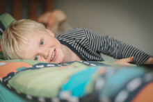 Little Boy Lying On Bed With Big Happy Smile