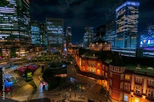 Fotografia 黄昏時、ライトアップされた東京駅と周囲の高層ビル群