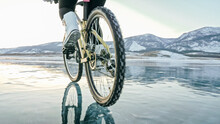 Woman Is Riding Bicycle On The Ice. Tires On Bike Are Covered Wi