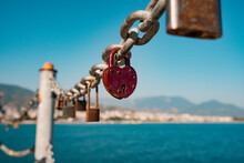 Red Heart Padlock On Chain In Front Of Blue Sea And Lighthouse, Symbol Of Eternal Love