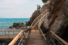 Wood Stairs On A Mountain Road Against The Background Of The Sea And Mountains