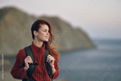 woman hiker holds a backpack on her shoulders and look at the sea from the side of the mountains in the background