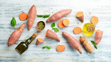 Sweet Potatoes On A White Wooden Background. Dietary Food. Top View. Free Space For Your Text.