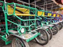 Italian Cycle Rickshaws Are In A Row For Rent In The Park. Active Lifestyle While Pedaling. Yellow, Blue, Green. Metal Frame
