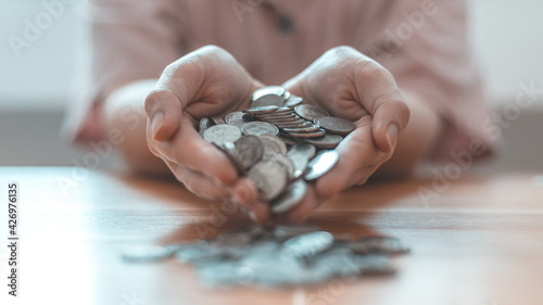 Valokuva Woman's hand full of coins, Business people saving money for future investment, saving money, Silver baht coins,Finance and investment, including taxes, Spending money like maturity concept