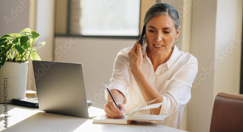 Businesswoman talking on cell phone and taking notes in office