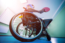 Disabled Man In A Wheelchair Play At Table Tennis. Tennis Balls Fixed In A Wheel