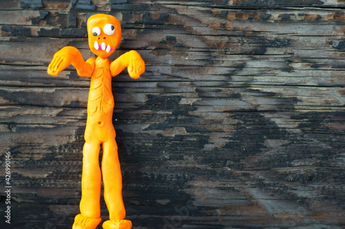 Fotografie, Obraz Toy funny zombie made of plasticine on a wooden background.