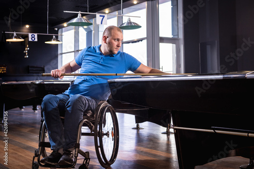Fototapeta Adult man with disability in a wheelchair play billiards in the club obraz
