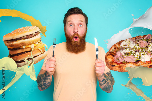 Photographie Man with tattoos is ready to eat sandwich and pizza with cutlery in hand