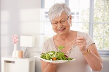 Happy Old Lady Eating Fresh Green Salad, Smiling.