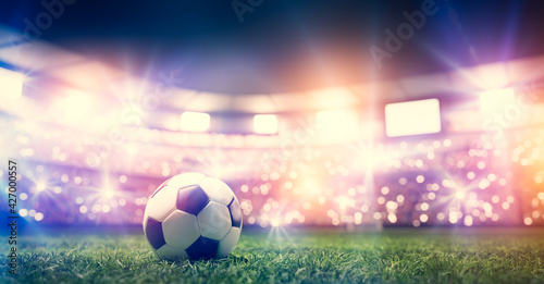 Fototapeta Football soccer ball on grass field on stadium obraz