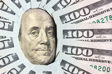 A Lot Of Folded One Hundred 100 USD Bills Layed Like Vintage Sun Face Beams Around Benjamin Franklin Portrait From 100 Dollar US Bill American Currency. Concept Of Wealth And Affluence Background.
