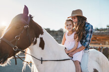 Mother And Daughter Riding A Horse At Ranch - Mother And Child Love