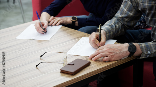 Fotografía An adult woman and a man, sitting at a table in the office, fill out documents or forms