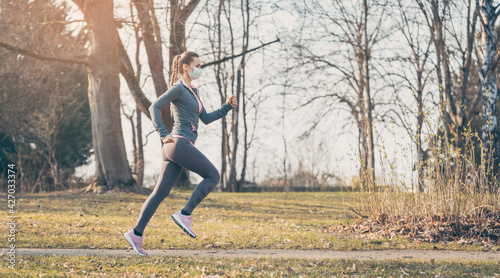 Fototapeta Woman running with face mask to stay healthy during covid-19 obraz