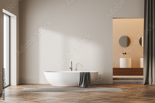 Beige wooden bathroom interior bathtub near window and sink