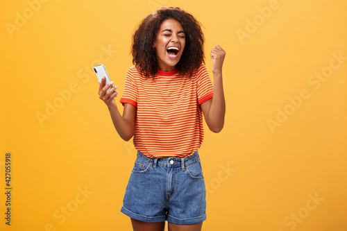 Fotografie, Obraz Portrait of ambitious happy young african american girl yelling from happiness a