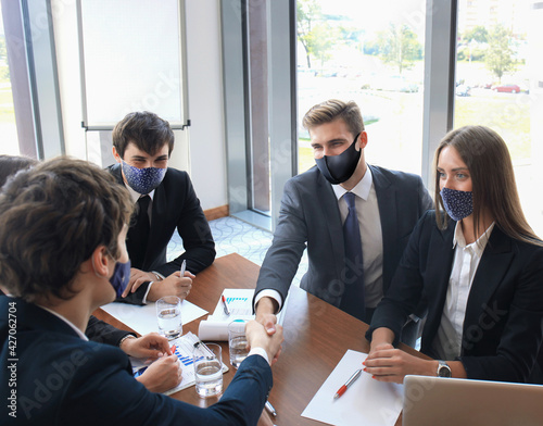 Obraz na plátne Businessman in preventive mask shaking hands to seal a deal with his partner and colleagues who also wear preventive masks in office