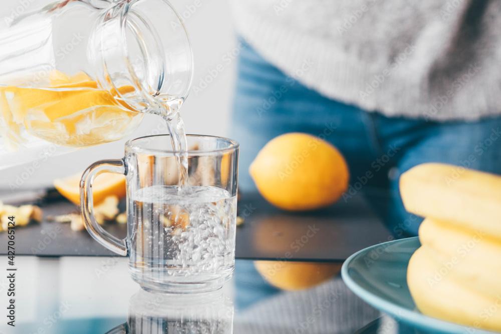 Fototapeta Woman making lemonade at home.
