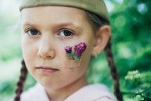 Little Caucasian Girl Portrait With Flowers On Cheek And Military Hat