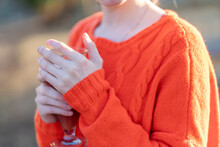 Orange Knitted Sweater Dressed On A Girl Close-up