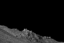 Cold Rocky Desert Mountains Under A Black Sky, Black And White Image.