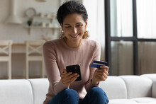 Safe Mobile Banking. Smiling Latina Lady Client Hold Mobile Phone Credit Bank Card Do Online Shopping Provide Internet Payment. Happy Young Woman Enjoy Easy Fast Secure Transferring Money In Ebank App