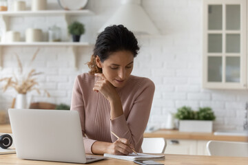 Confident hispanic female planning work by laptop using written list of tasks. Young woman remote student listen to video lesson on pc take notes check previous records correct mistakes in copybook