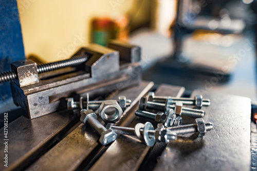 Obraz Metal chrome bolts and nuts on drilling machine at the workplace of a toolman locksmith - fototapety do salonu