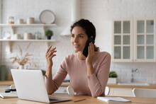Inspired Hispanic Woman Remote Worker Student Sit By Laptop Calling Teacher Colleague To Discuss New Plan Idea. Motivated Young Latin Woman Freelancer Make Answer Business Call At Work In Home Office