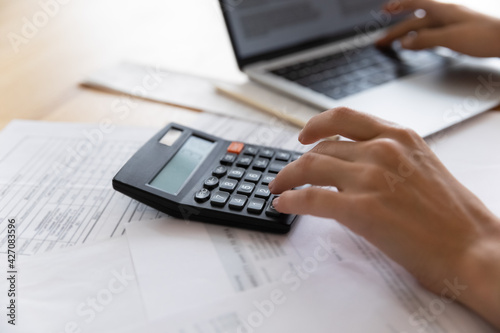 Auditor workplace. Close up of woman professional bookkeeper at work counting expenses costs planning savings economy making payment. Focus on female accountant hand pressing electronic calculator key