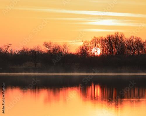 Fototapeta leniwy wschód słońca z mgła przy brzegu  obraz