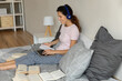 Leinwandbild Motiv Young hispanic woman in earphones sit on bed surrounded by paper literature consult with tutor on distance via video call on pc. Female student give correct answer on teacher question at remote lesson